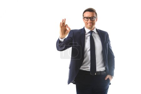 Photo for Smiling businessman in eyeglasses showing ok gesture isolated on white background - Royalty Free Image