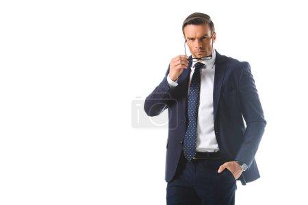 seriöser Geschäftsmann mit Hand in Tasche, Brille auf weißem Hintergrund