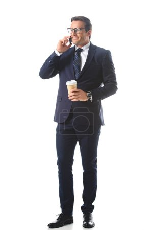 Photo for Smiling businessman in eyeglasses talking on smartphone and holding paper cup of coffee isolated on white background - Royalty Free Image