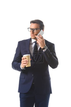 serious businessman in eyeglasses talking on smartphone and holding paper cup of coffee isolated on white background