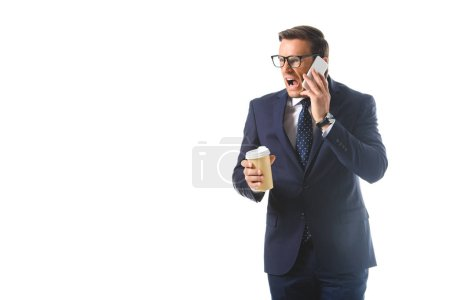 angry businessman in eyeglasses talking on smartphone and holding paper cup of coffee isolated on white background