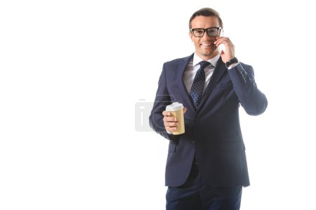 happy businessman in eyeglasses talking on smartphone and holding paper cup of coffee isolated on white background