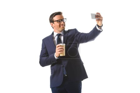 smiling businessman in eyeglasses holding paper cup of coffee and taking selfie on smartphone isolated on white background