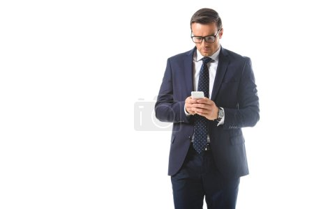 serious businessman in eyeglasses checking smartphone isolated on white background