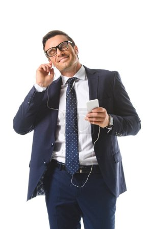 happy businessman in eyeglasses listening music in earphones with smartphone isolated on white background