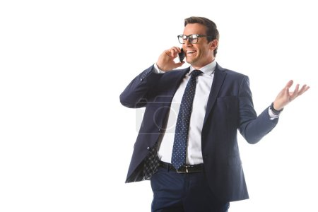 smiling businessman in eyeglasses talking on smartphone and gesturing by hand isolated on white background