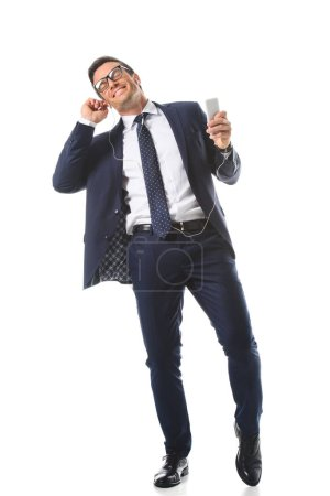 relaxed businessman in eyeglasses listening music in earphones with smartphone isolated on white background