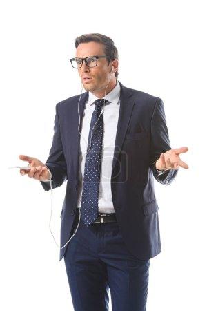 homme d'affaires émotionnelle dans lunettes avec écouteurs parler sur smartphone et faire haussement d'épaules gesticulent isolé sur fond blanc