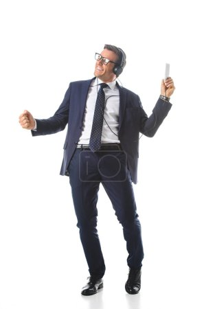 happy businessman in eyeglasses listening music in headphones with smartphone and gesturing by hand isolated on white background