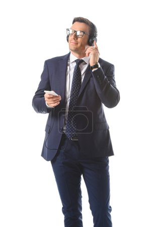 relaxed businessman in eyeglasses listening music in headphones with smartphone isolated on white background