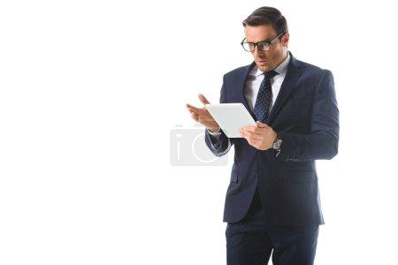 sorprendido hombre de negocios en gafas gestos a mano y mirando la pantalla digital de la tableta aislado sobre fondo blanco