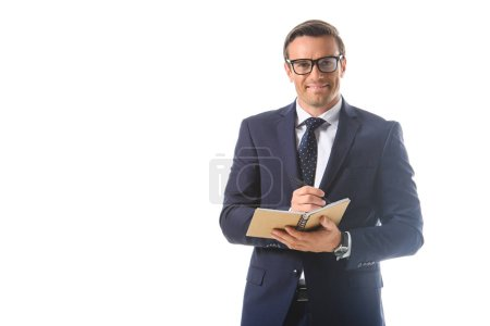 smiling businessman in eyeglasses writing in textbook isolated on white background