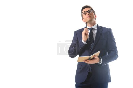 Photo for Thoughtful businessman in eyeglasses holding pen and textbook isolated on white background - Royalty Free Image