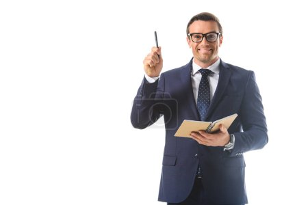 smiling businessman in eyeglasses doing idea gesture by pen and holding textbook isolated on white background