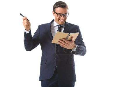 happy businessman in eyeglasses doing idea gesture by pen and holding textbook isolated on white background
