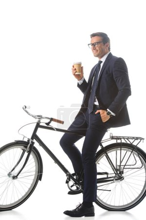 happy businessman in eyeglasses sitting on bicycle and holding paper cup of coffee isolated on white background