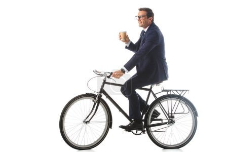 Photo for Smiling businessman in eyeglasses riding bicycle and holding paper cup of coffee isolated on white background - Royalty Free Image