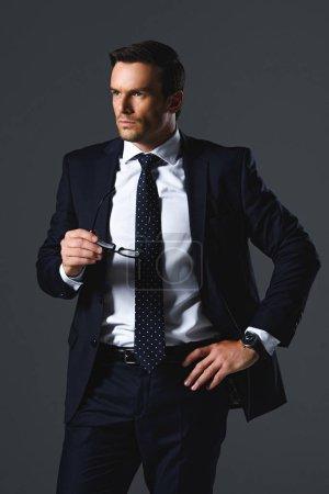 serious businessman holding eyeglasses isolated on grey background