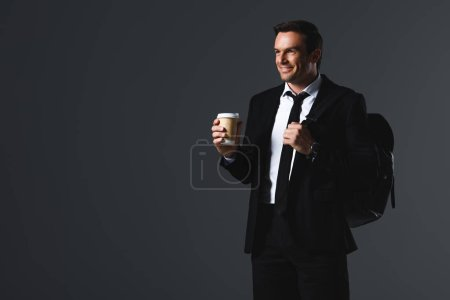 smiling businessman with rucksack holding paper cup of coffee isolated on grey background