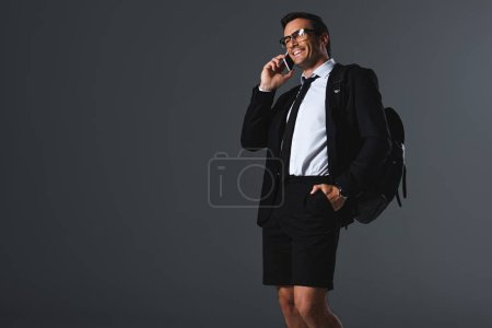 smiling stylish man in shorts with backpack talking on smartphone on grey background