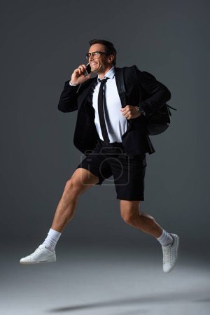 excited fashionable man in eyeglasses talking on smartphone and jumping with backpack on grey background