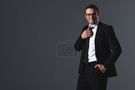 happy businessman in eyeglasses with hand in pocket adjusting tie isolated on grey background