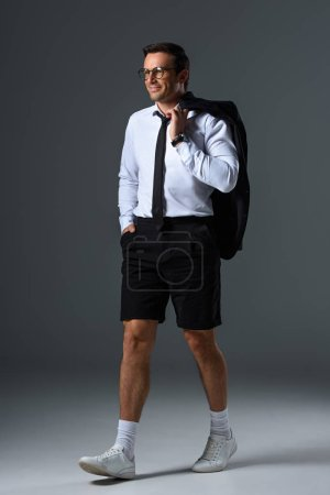smiling stylish man with eyeglasses in shorts holding jacket on shoulder on grey background