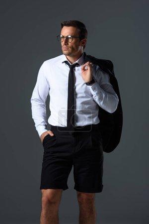 confident stylish man with eyeglasses in shorts holding jacket on shoulder isolated on grey background