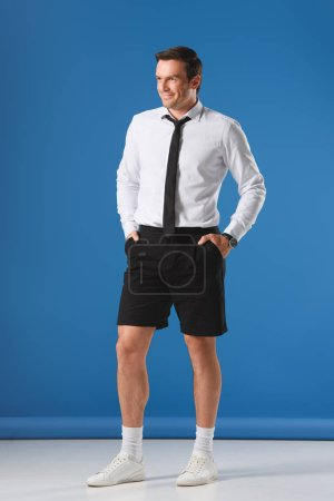 smiling stylish man in shorts with hands in pockets on blue background
