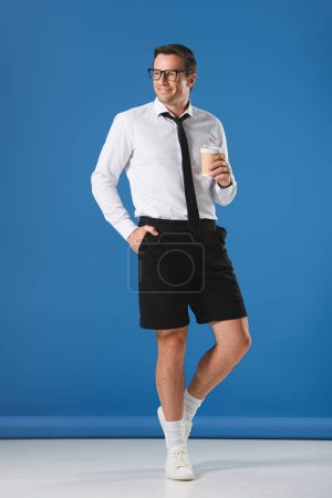 handsome smiling man in eyeglasses holding coffee to go while standing with hand in pocket of shorts and looking away on blue