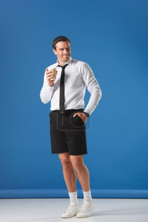 handsome smiling man holding disposable coffee cup while standing with hand in pocket of shorts on blue
