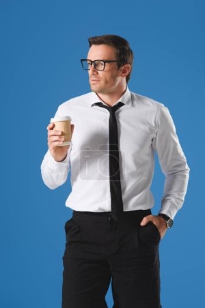 serious businessman in eyeglasses holding paper cup and looking away while standing with hand in pocket isolated on blue