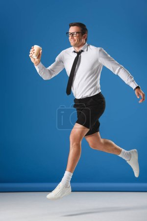 happy man holding disposable coffee cup while jumping and looking away on blue