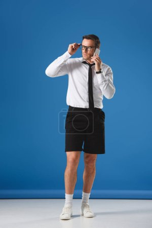 serious man in shorts and eyeglasses talking by smartphone and looking away on blue