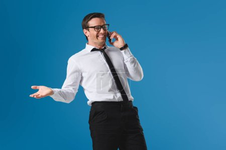 happy buisnessman in eyeglasses laughing while talking by smartphone isolated on blue
