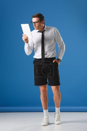 focused man in eyeglasses and shorts using digital tablet while standing with hand in pocket on blue