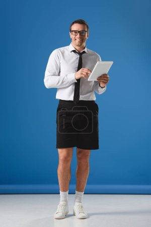 handsome businesman in eyeglasses and shorts using digital tablet and smiling at camera on blue