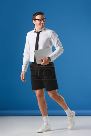 full length view of happy man in eyeglasses and shorts holding laptop and looking away on blue