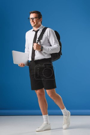 smiling man with backpack holding laptop and looking away on blue