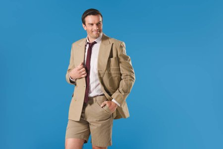 handsome man in suit jacket and shorts standing with hand in pocket and looking away isolated on blue