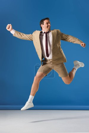 excited man in shorts and suit jacket jumping and looking away on blue