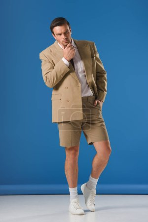 thoughtful man in shorts standing with hand on chin and looking away on blue