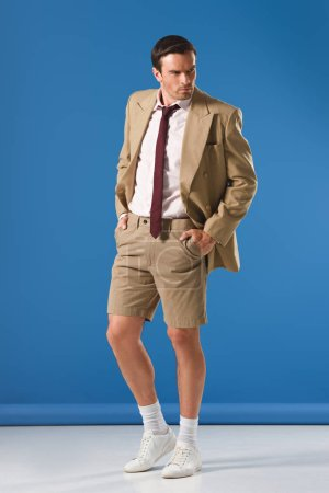 full length view of handsome man in suit jacket and shorts standing with hands in pockets and looking away on blue
