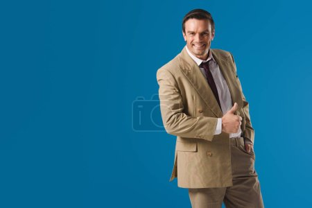 handsome happy man showing thumb up and smiling at camera isolated on blue