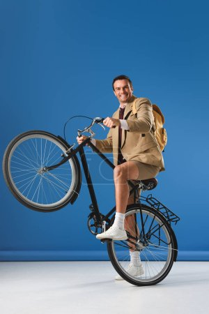 happy man riding bicycle and smiling at camera on blue