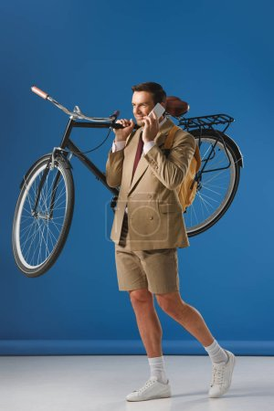 smiling man carrying bicycle and talking by smartphone on blue