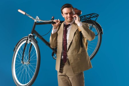 smiling man carrying bicycle and talking by smartphone isolated on blue