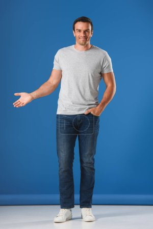 handsome man standing with hand in pocket and smiling at camera on blue