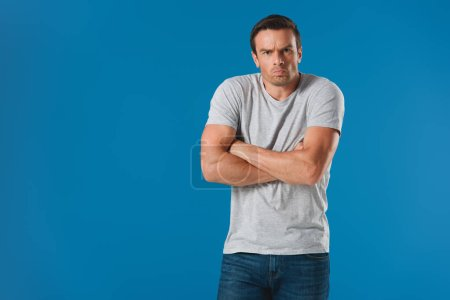 frowning man standing with crossed arms and looking at camera isolated on blue