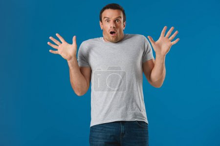 shocked man raising hands and looking at camera isolated on blue